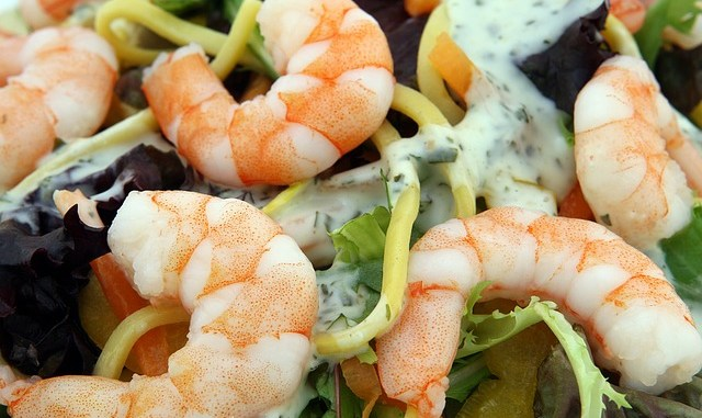 Cooked prawns on a salad bed with dressing.