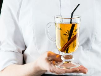 The unidentified waiter holding a glass with hot Amaro cocktail with apple juice and cinnamon