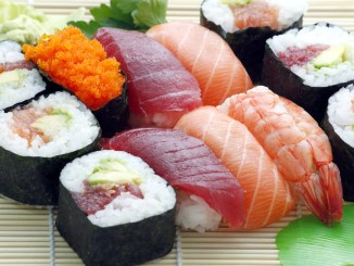 Different types of sushi, nigiri and sashimi on a rush plate