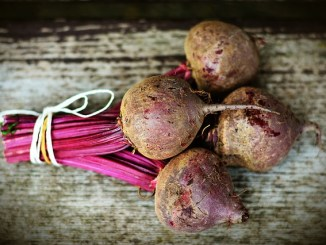 Beets tied up with string and lying on a grey brown wooden table