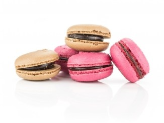 Pink and brown macaroons on a white background.