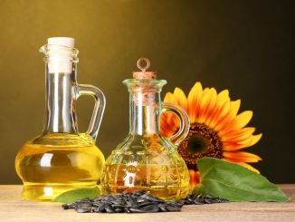 Sunflower oil and sunflower on yellow background