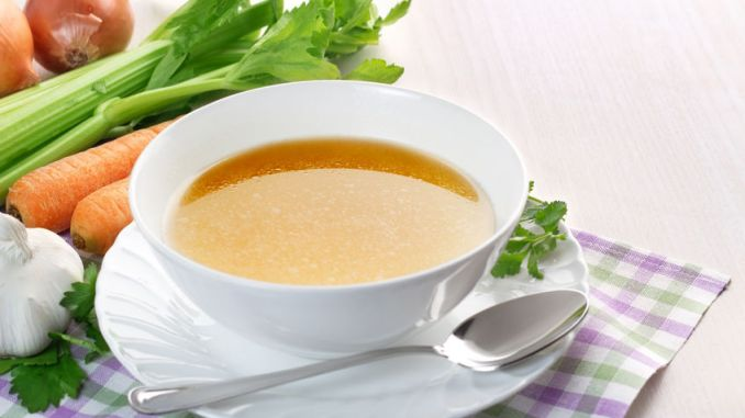 Bowl of broth (consomme) and fresh vegetables on wooden table