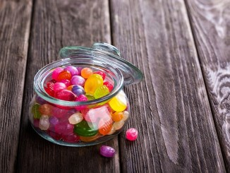 Sweets or candy in a jar on a wooden table.