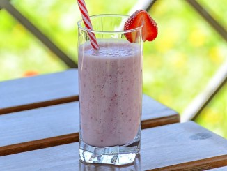 kefir strawberry smoothie in a straight glass with a strawberry garnish and straw on a wooden table.
