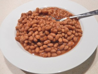 Boston-baked-beans in a white dish with spoon. Prepared with a slow cooker or multi-function cooker.