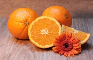 Oranges with an orange gerbera on a table as a source of vitamin C.