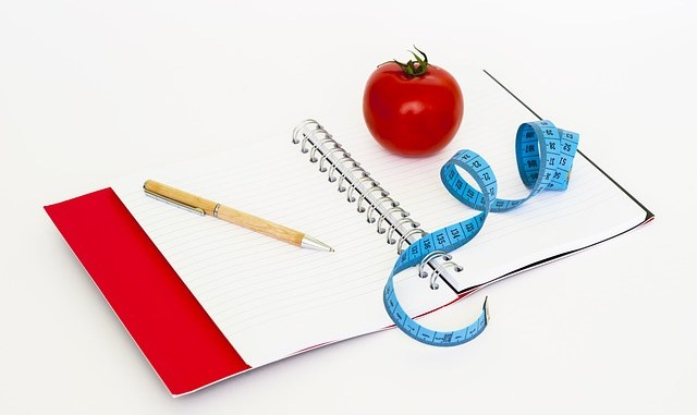 Notebook, apple, measuring tape and pencil. Images used to support various diets including Atkins Diet, the Slimfast diet