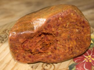 Nduja cut in half and sitting on a wooden plate.
