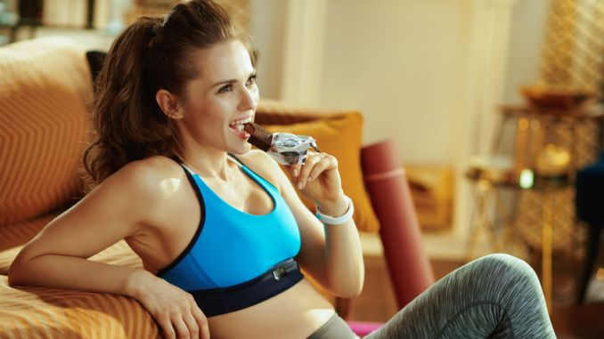 happy fit woman in sport clothes in the modern house eating chocolate raw protein bar.