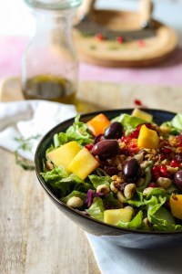 A glass dressing bottle, green salad with olives, mango, nuts