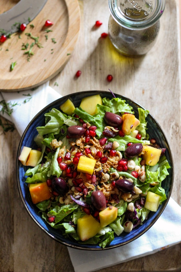 Mango, Pomegranate, Greek olive in a bowl with green lettuce.
