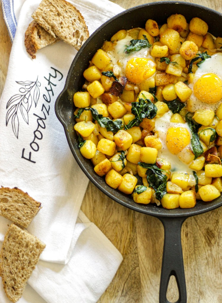 cast iron with potatoes, eggs, and spinach baked in the oven