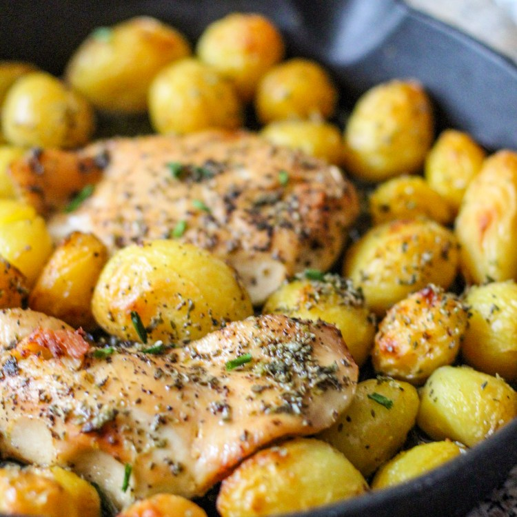 roasted chicken breast with roast baby potatoes garnished with oregano and olive oil and baked in a cast iron pan