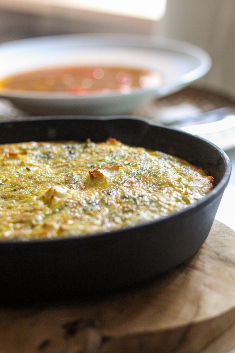 baked frittata with a bowl of lentil soup in the background