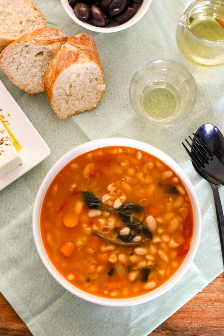 White Bean Soup with celery, slices of bread, feta cheese and greek olives in the background.