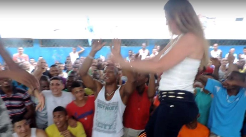 """Pic shows: Claudia Patricia Giraldo Ossa, prison director, dances with inmates. A blonde prison director who twerked in front of hundreds of sex-starved jail inmates is facing an inquiry in Colombia. Curvy Claudia Patricia Giraldo Ossa - head of the prison in Cali - appears in a series of steamy photos from inside the jail dancing erotically at a prisoners' """"cultural event."""" Ossa - wearing a shoulder revealing halter necked top, skin tight jeans and stilettos - jumped up on stage and was pictured performing a sexy bump and grind routine with a series of baying prisoners. Others packing Villahermosa Jail's Courtyard 5 cheered her on without a single prison guard in sight. Colleagues say Ossa had not intended to perform at the event but had got carried away when inmates called for her to get up on a makeshift stage. Local media reports she has not commented on the scandal. Officials say she now faces an inquiry into discipline at her jail. The scandal emerge as Colombia's new Minister of justice, Jorge Londono, declared a state of emergency in the country's prisons. Overcrowding is said to be causing severe problems with drug abuse and violence with msot jails struggling with occupancy levels of more than 150 per cent. (ends)"""