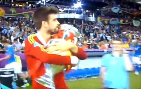 Gerard Piqué hugs the trophy as Spain win Euro 2012 and become the first team to win three major tournaments in a row