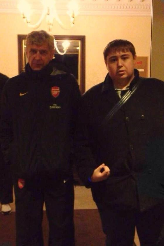 A rude gesture is made in a Spurs fan's photo with Wenger