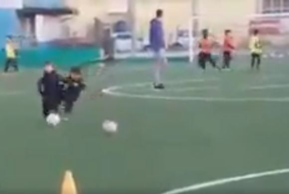 Child trips other boy during dribbling training drill