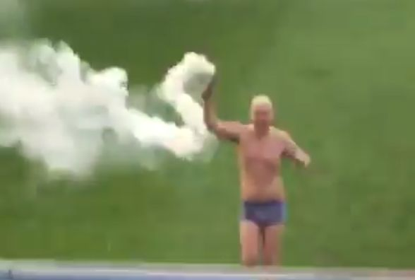 A Mossley fan in his underpants invades the pitch at Colwyn Bay with a smoke bomb