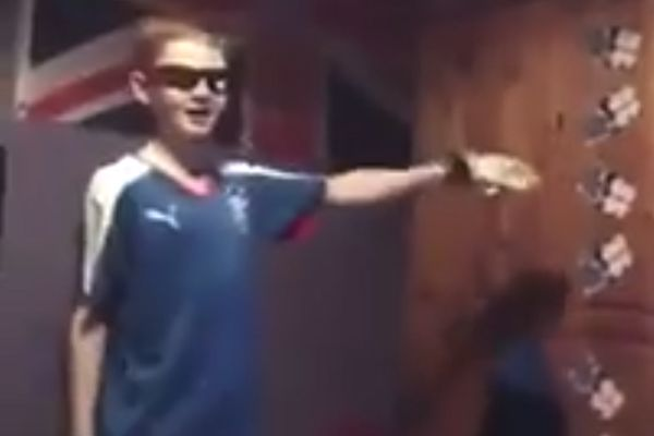 A young Rangers fan punches a wardrobe in what could be his bedroom