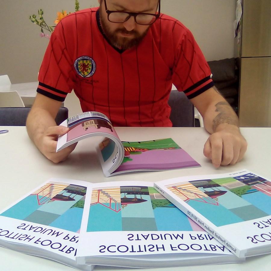 Steve Stewart reading a copy of Scottish Football Stadium Prints book by Steve Stewart