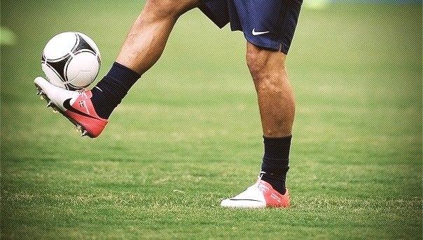Футболист набивает мяч ногой