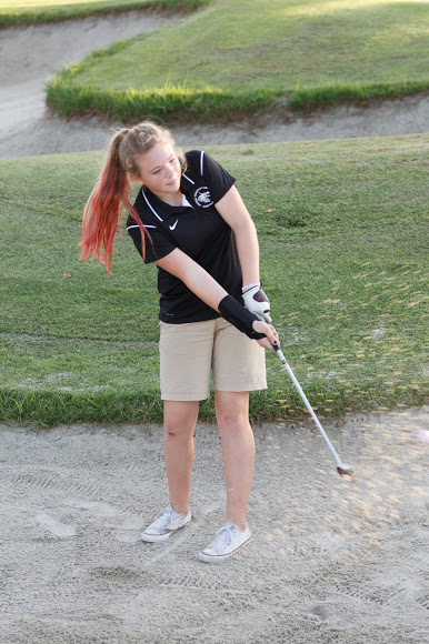 Sophomore Kyleigh Zickafoose attempts to hit the ball out of the bunker. Credit: Grayson McCoy/The Foothill Dragon Press