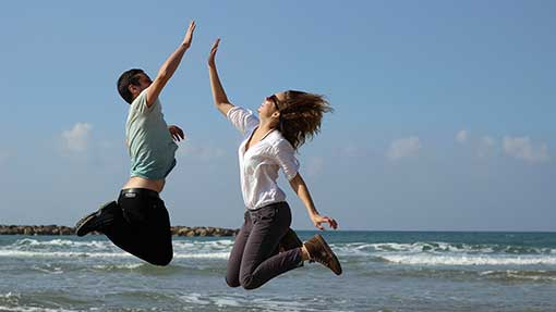 boy and girl jumping and clapping hands at the beach