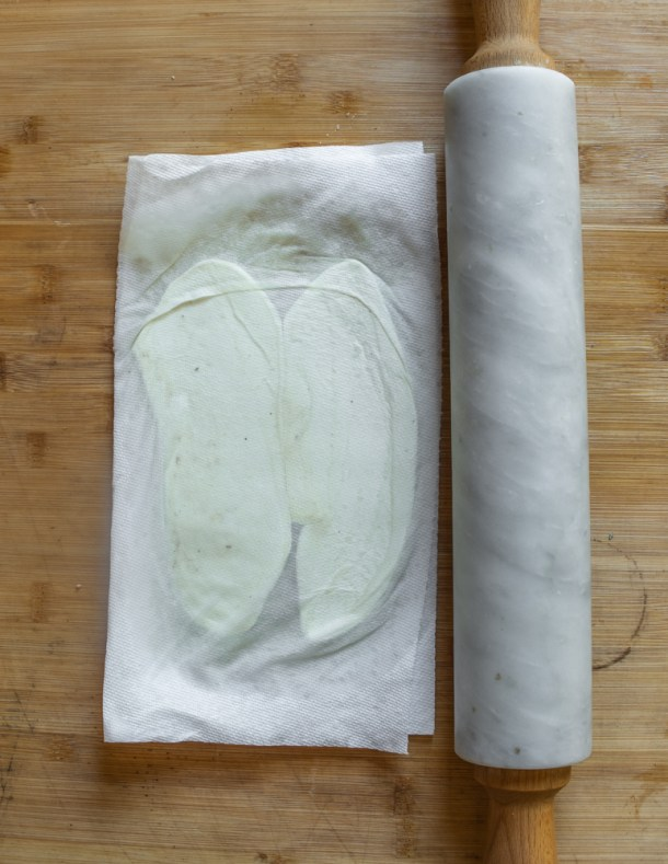 Pressing puffball mushrooms between towels with a rolling pin to remove water