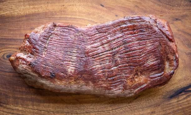 smoked venison leg roast on a wood board