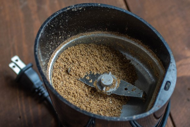 Grinding dried hackberries in a spice grinder