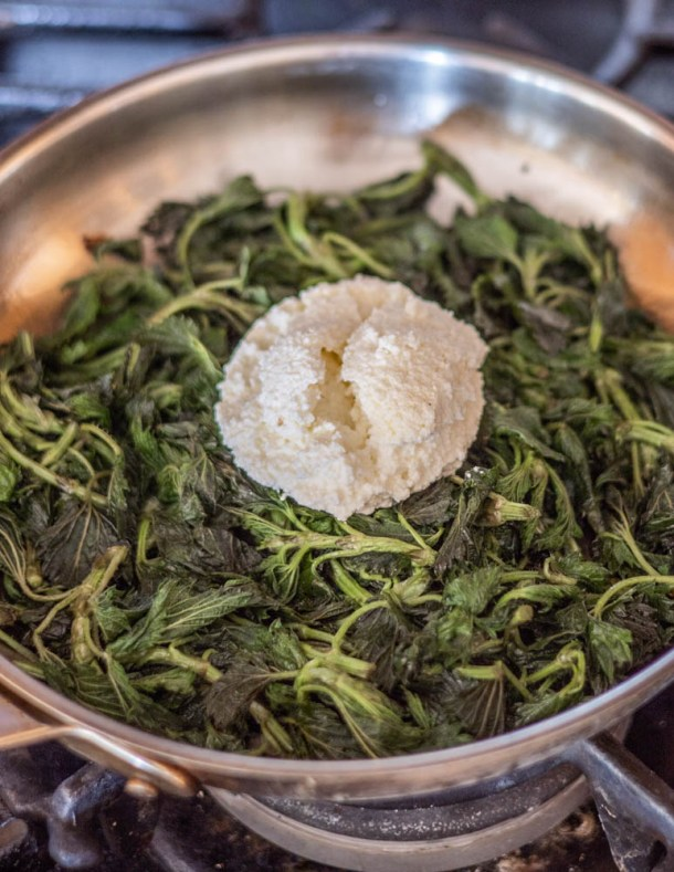 Adding ricotta to a pan of steamed nettles