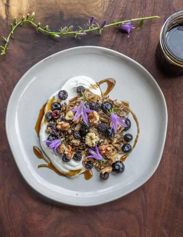 Breakfast wild rice with black walnuts, yogurt, black caps, and green walnut molasses