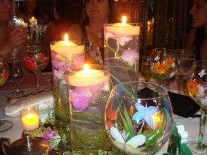 Our centerpieces were large cylinder vases in three different sizes. There were floating orchids with grasses and acrylic gems. Each was topped with a floating candle. We rented the glass mirrored bottoms from the florist who created the centerpieces. I could have made them easily myself if I had any floral ability. They were inexpensive and everyone wanted to take them home. We use two of them ourselves that I repurposed for our outdoor table and for Christmas! I added votives around them that I bought for a huge discount at a Michaels sale.