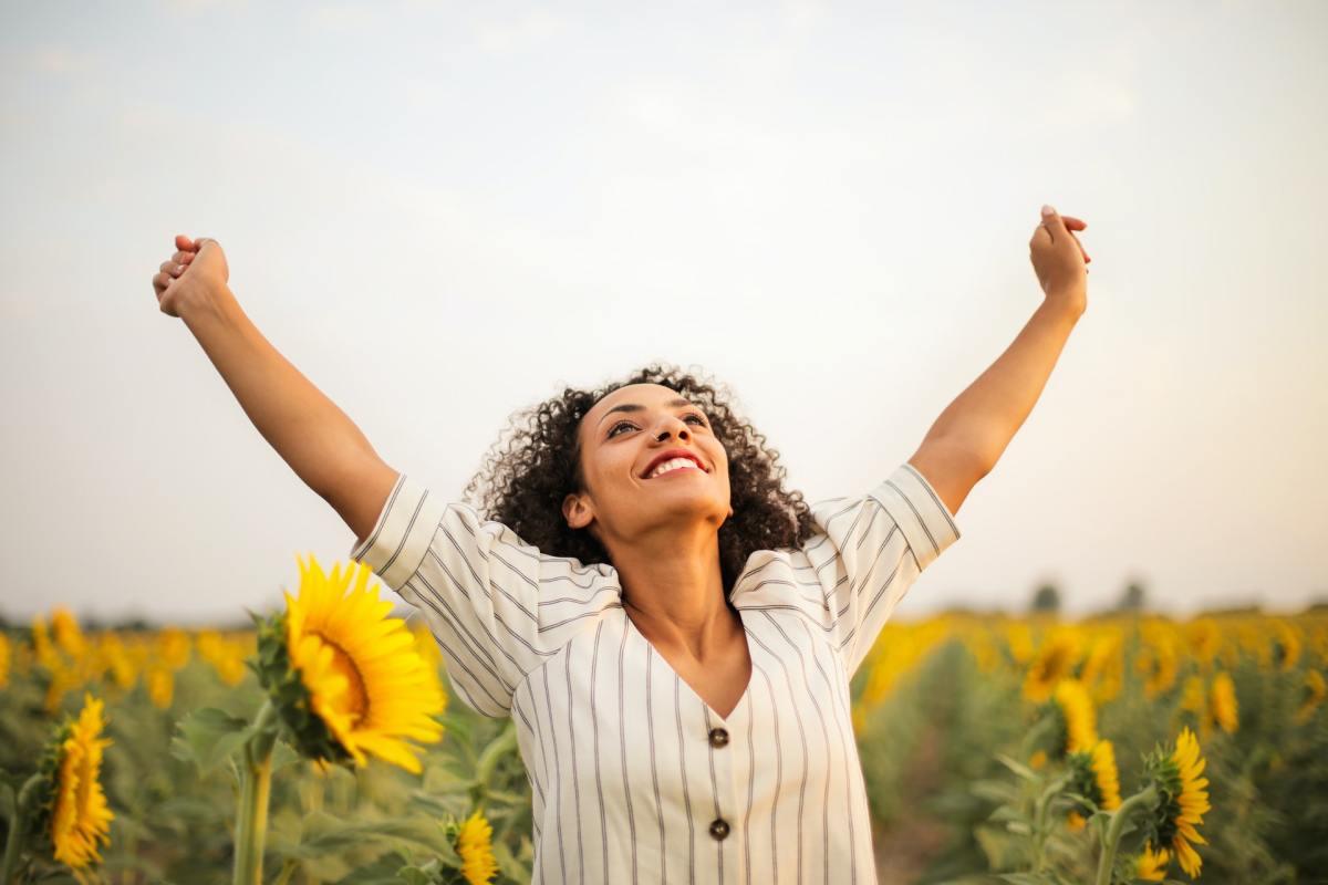 Chica en un campo de girasoles con los brazos estirados