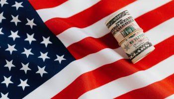 Bandera americana con un fajo de billetes enrollado