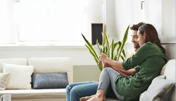 Una pareja sentados en el sofá de su salón miran su tablet