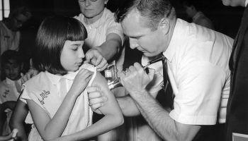 Un señor pincha en el brazo una aguja a una niña