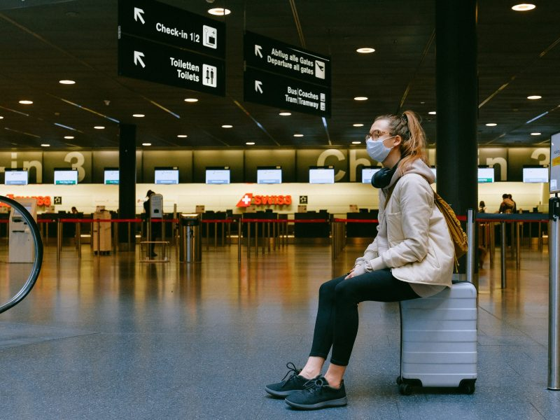 Una chica espera sentada en su maleta dentro del aeropuerto a que salga su avion. Foto: Anna Shvets (Pexels)