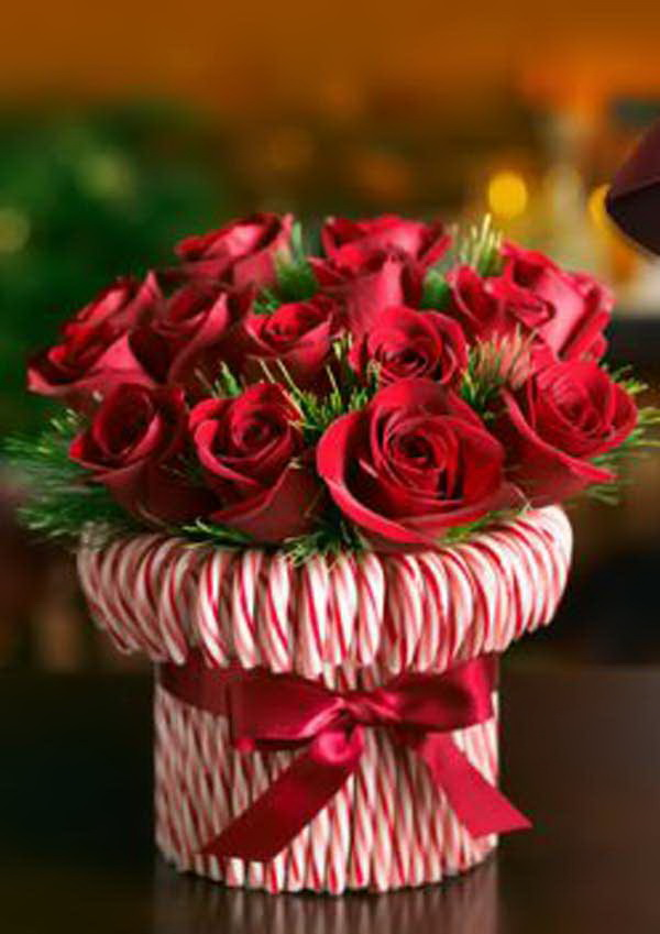 Candy Cane Vase. Make a candy canes vase and fill it with red roses for an easy and cute Christmas flower table decor.
