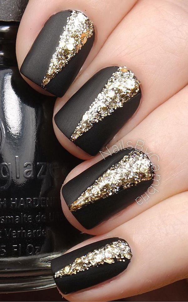 Elegant Black Matte Nails with Gold Embellishments on Top.