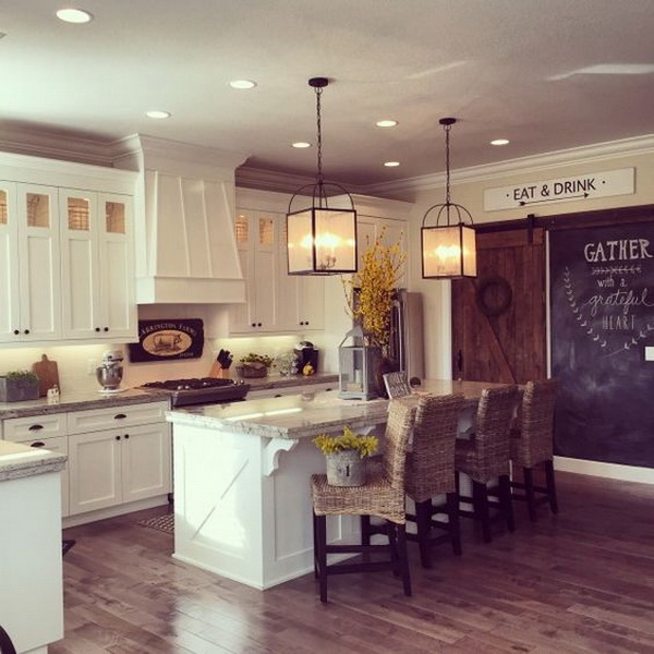 White kitchen with lots of farmhouse flair including the rolling barn wood door, chalkboard wall and double lanterns over the large island. More via https://forcreativejuice.com/elegant-white-kitchen-interior-designs/