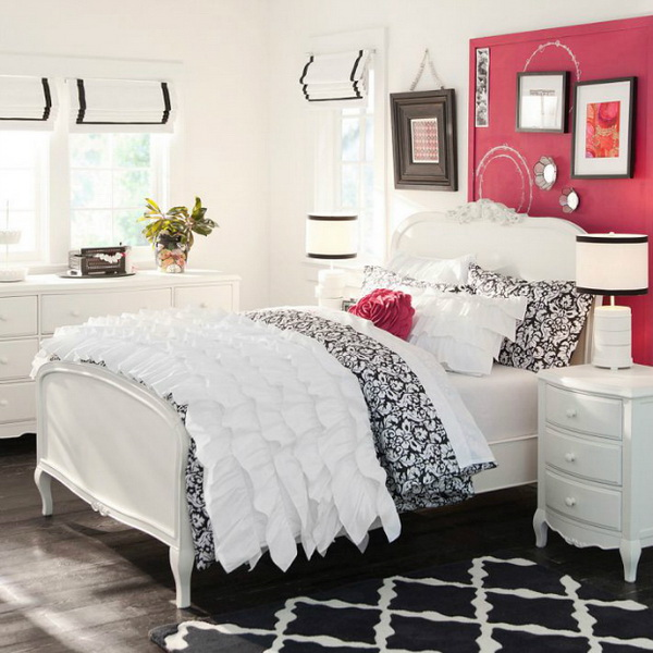 Pink painted headboard walls with two framed wall art pop up this white bedroom.