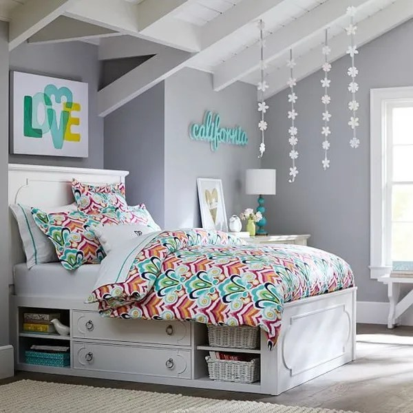 Chic grey walls, bright floral bedding, a bed with lots of storage.