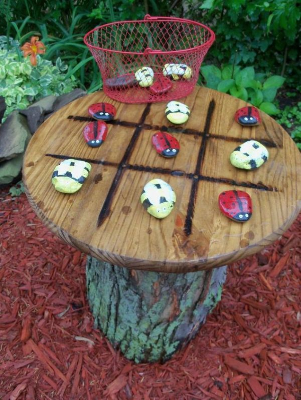 Tic Tac Toe Garden Table: Tic tac tree trunk table with some stones painted as ladybugs and bees. These will be great for out in the garden by the kids' fairy garden.