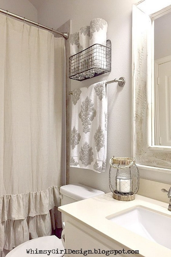 Add a touch of farmhouse flair to your guest bathroom using this metal hanging basket to store and display towels.