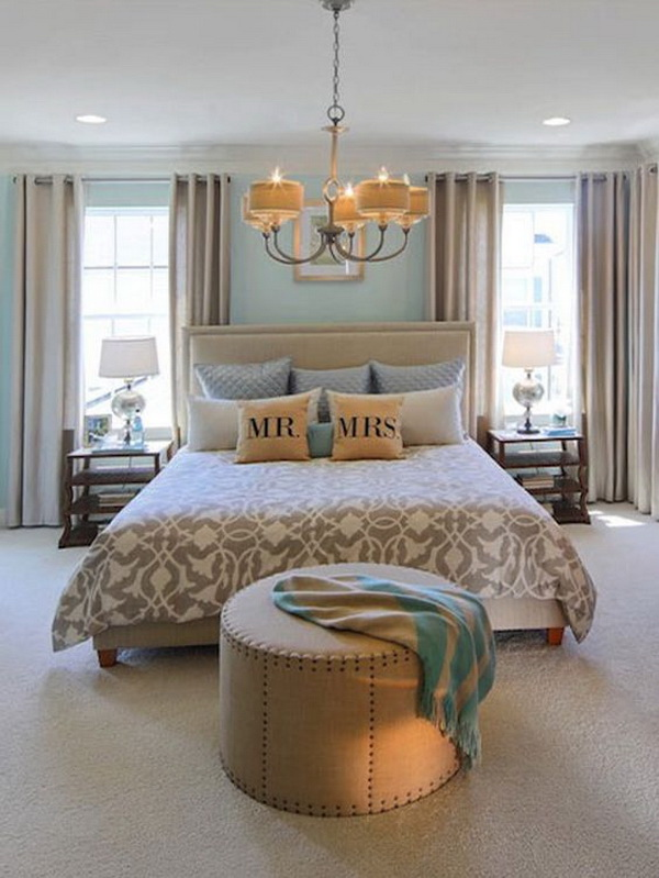 Teal painted master bedroom with a classic chandelier above the bed.