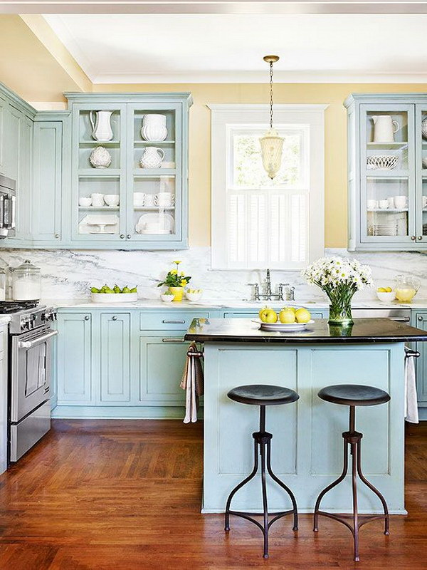 Pale Blue Kitchen Cabinets with Glass Cupboards and Marble Backsplash.